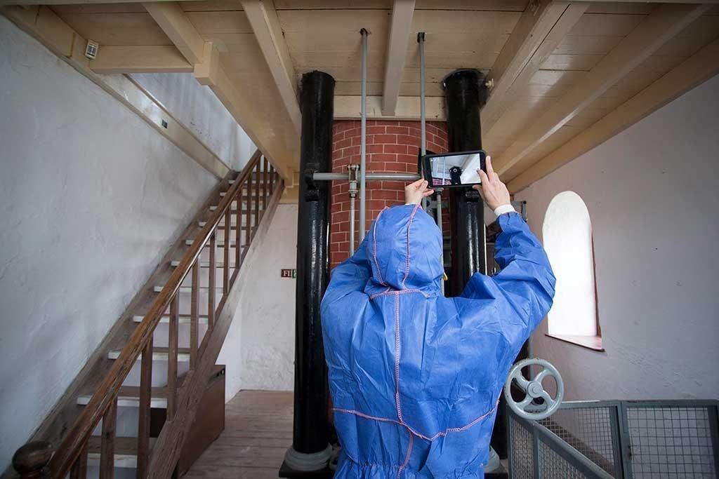 Asbestos surveyor inspecting pipes