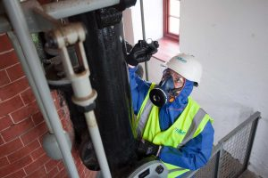 A trainee asbestos surveyor inspecting pipes in an old mine in Cornwall