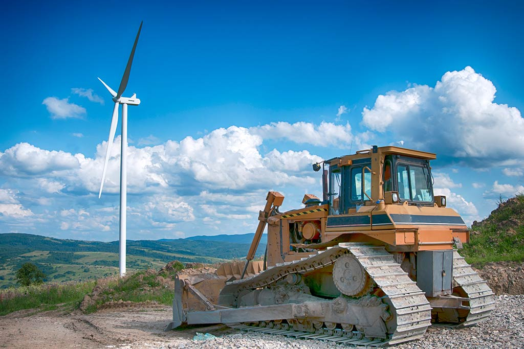 Contaminated land project management. Bulldozer in front of a wind turbine